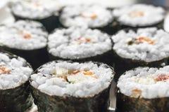 Sushi Rolls de Chumaki com atum, salmões, arroz, pepino, abacate e Nori Seaweed em uma placa fotos de stock royalty free