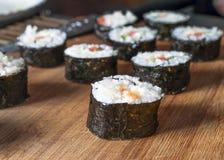 Sushi Rolls de Chumaki com atum, salmões, arroz, pepino, abacate e Nori Seaweed em uma placa de madeira com o Kitchenware borrado foto de stock royalty free