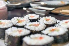 Sushi Rolls de Chumaki com atum, salmões, arroz, pepino, abacate e Nori Seaweed em uma placa com o molho de soja que mergulha o p foto de stock
