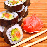 Sushi, rolls, ginger and chopstick on bamboo mat Stock Photos