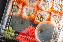 Sushi rolls, ginger and soy in plastic container top view Royalty Free Stock Photos