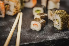 Sushi rolls hosomaki and uramaki. Traditional japanese sushi rolls hosomaki and uramaki and chopsticks on stone desk Stock Photo