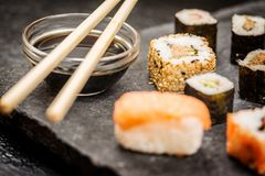 Sushi rolls hosomaki and uramaki. Traditional japanese sushi rolls hosomaki,uramaki, nigiri  and chopsticks and soy sauce on stone desk Stock Photography