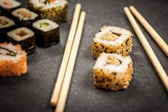 Sushi rolls hosomaki and uramaki. Traditional japanese sushi rolls hosomaki,uramaki  and chopsticks  on stone desk Stock Photo