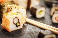 Sushi rolls hosomaki and uramaki. Traditional japanese sushi rolls hosomaki and uramaki and chopsticks on stone desk Royalty Free Stock Photos