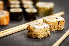 Sushi rolls hosomaki and uramaki. Traditional japanese sushi rolls hosomaki,uramaki  and chopsticks  on stone desk Royalty Free Stock Photography