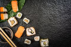 Sushi rolls hosomaki and uramaki. Traditional japanese sushi rolls hosomaki,uramaki, nigiri  and chopsticks and soy sauce on stone desk top view Royalty Free Stock Photography