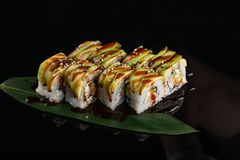Sushi rolls japanese food over black background. Sushi roll with salmon, tofu, vegetables and avocado closeup. Japan restaurant stock photo