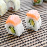 Sushi rolls lies on a bamboo straw serwing mat. Traditional Asian food. Shallow depth of field.  royalty free stock photo