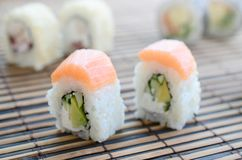 Sushi rolls lies on a bamboo straw serwing mat. Traditional Asian food. Shallow depth of field.  stock photo