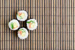 Sushi rolls lies on a bamboo straw serwing mat. Traditional Asian food. Top view. Flat lay minimalism shot with copy space.  stock image