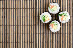 Sushi rolls lies on a bamboo straw serwing mat. Traditional Asian food. Top view. Flat lay minimalism shot with copy space.  royalty free stock photography