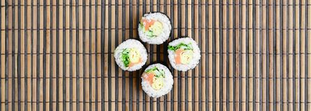 Sushi rolls lies on a bamboo straw serwing mat. Traditional Asian food. Top view. Flat lay minimalism shot with copy space.  royalty free stock images