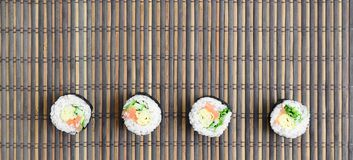 Sushi rolls lies on a bamboo straw serwing mat. Traditional Asian food. Top view. Flat lay minimalism shot with copy space.  stock images