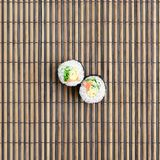 Sushi rolls lies on a bamboo straw serwing mat. Traditional Asian food. Top view. Flat lay minimalism shot with copy space.  royalty free stock image