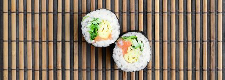 Sushi rolls lies on a bamboo straw serwing mat. Traditional Asian food. Top view. Flat lay minimalism shot with copy space.  royalty free stock photos