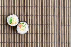 Sushi rolls lies on a bamboo straw serwing mat. Traditional Asian food. Top view. Flat lay minimalism shot with copy space.  royalty free stock photo