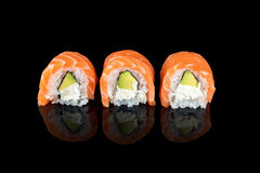 Sushi rolls made of fresh raw salmon, cream cheese and avocado isolated on black with reflections Stock Images