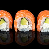 Sushi rolls made of fresh raw salmon, cream cheese and avocado isolated on black with reflections Stock Photography