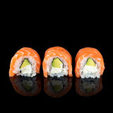 Sushi rolls made of fresh raw salmon, cream cheese and avocado isolated on black with reflections. Free space for text. Stock Photos