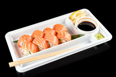 Sushi rolls made of fresh raw salmon, cream cheese and avocado in white plastic container ready to eat on black Stock Photography