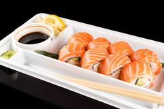 Sushi rolls made of fresh raw salmon, cream cheese and avocado in white plastic container ready to eat on black Stock Photos