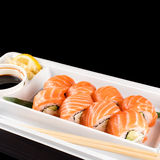Sushi rolls made of fresh raw salmon, cream cheese and avocado in white plastic container ready to eat on black Stock Image