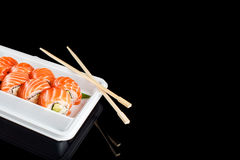 Sushi rolls made of fresh raw salmon, cream cheese and avocado in white plastic container ready to eat on black Royalty Free Stock Images