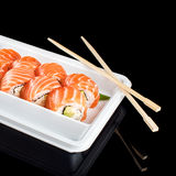Sushi rolls made of fresh raw salmon, cream cheese and avocado in white plastic container ready to eat on black Royalty Free Stock Image