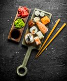 Sushi, rolls and maki on the cutting Board with chopsticks and sauces. On black rustic background royalty free stock photos