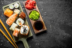 Sushi, rolls and maki on the cutting Board with chopsticks and sauces. On black rustic background stock image