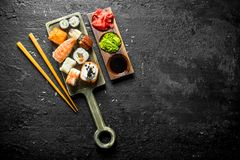 Sushi, rolls and maki on the cutting Board with chopsticks and sauces. On black rustic background stock photos