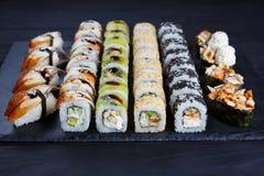 Sushi rolls, maki, nigiri and gunkan set served on black stone s stock photos