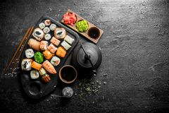 Sushi, rolls and maki with soy sauce, ginger and green tea. On black rustic background royalty free stock images
