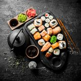Sushi, rolls and maki with soy sauce, ginger and green tea. On black rustic background stock photo