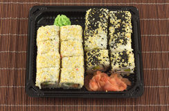 Sushi rolls in plastic container on wicker straw mat closeup Royalty Free Stock Images