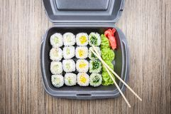 Sushi rolls in a container on a wooden table. top view royalty free stock image