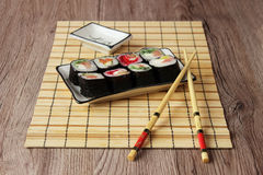 Sushi rolls on a plate on bamboo brown straw mat with chopsticks close up Royalty Free Stock Photography