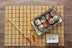 Sushi rolls on a plate on bamboo brown straw mat  with chopsticks close up Stock Photos
