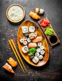 Sushi and rolls on a plate with boiled rice in a bowl and chopsticks. On dark rustic background royalty free stock photo
