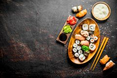 Sushi and rolls on a plate with boiled rice in a bowl and chopsticks. On dark rustic background royalty free stock photography