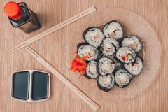 Sushi rolls on a round plate with sticks and soy sauce, top view royalty free stock images