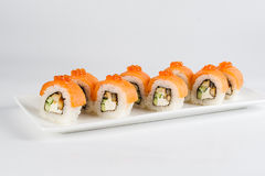 Sushi rolls with salmon, avocado and cream cheese, decorated with red caviar, served on white slate. Stock Photos