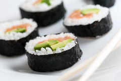 Sushi rolls with salmon, avocado, rice in seaweed and chopsticks on a plate. Royalty Free Stock Photos