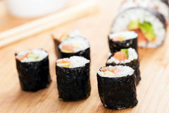 Sushi rolls with salmon, avocado, rice in seaweed and chopsticks Royalty Free Stock Photos