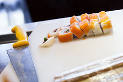 Sushi rolls with salmon lay on cutting board. Traditional Japanese sushi rolls with salmon lay on white cutting board with chief knife. Selective focus Stock Photos