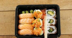 Sushi rolls with salmon in plastic tray. On wooden background stock video