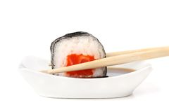 Sushi rolls with salmon, rice and nori in chopsticks dipped in s Royalty Free Stock Photography