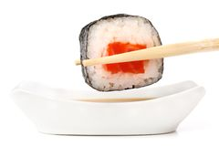 Sushi rolls with salmon, rice and nori in chopsticks dipped in s Stock Photo