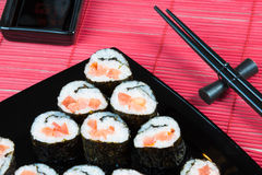 Sushi rolls. With salmon and tomato on a black square plate Royalty Free Stock Photo